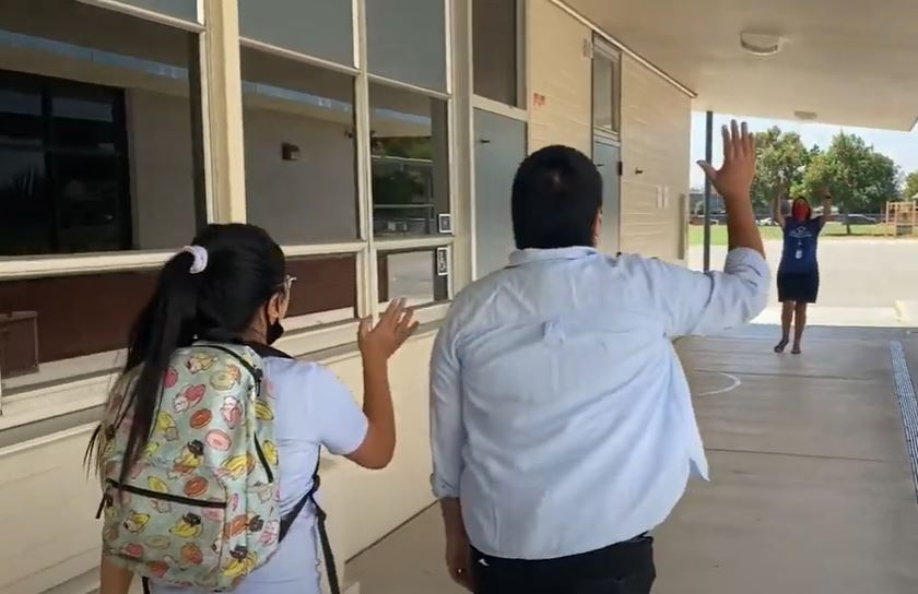 Principal Dodd waving at two students
