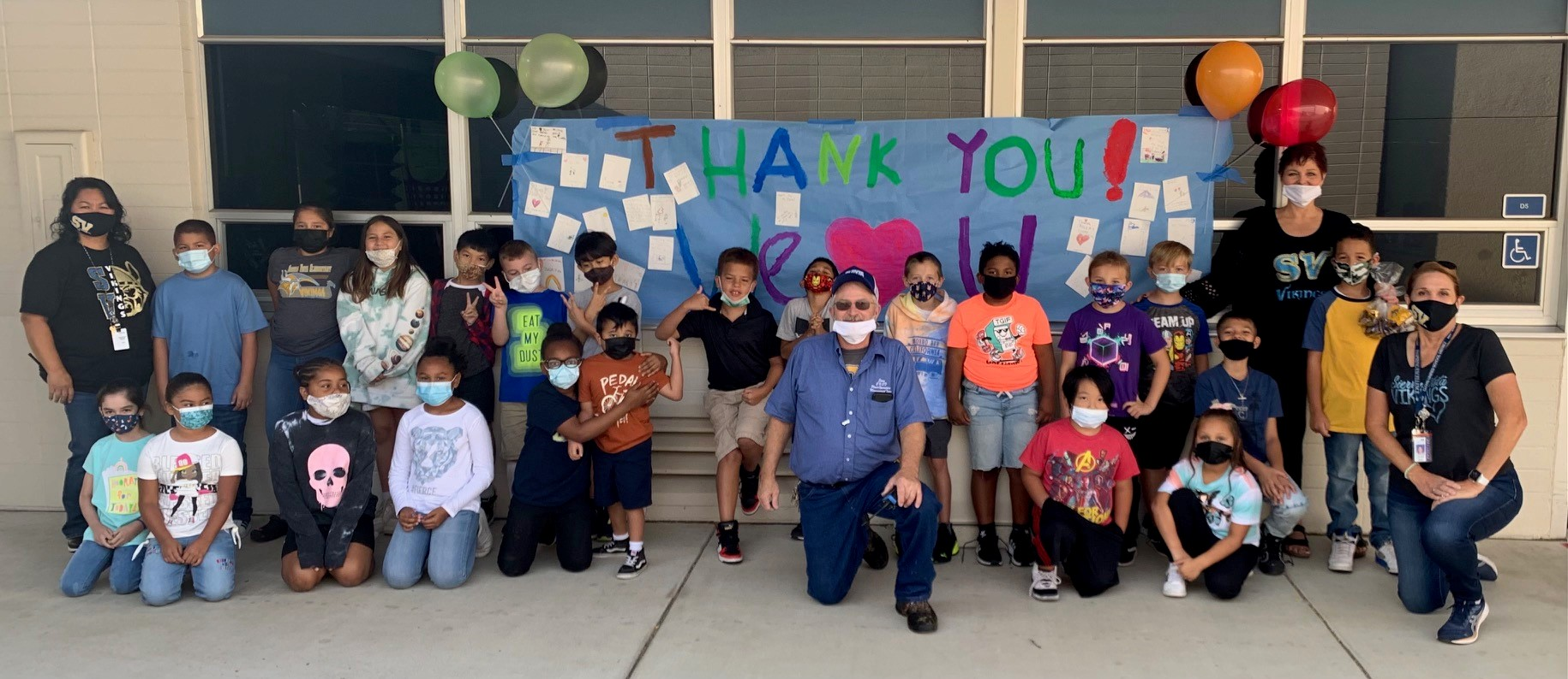 Students, teachers, principal pose with custodian to say thank-you