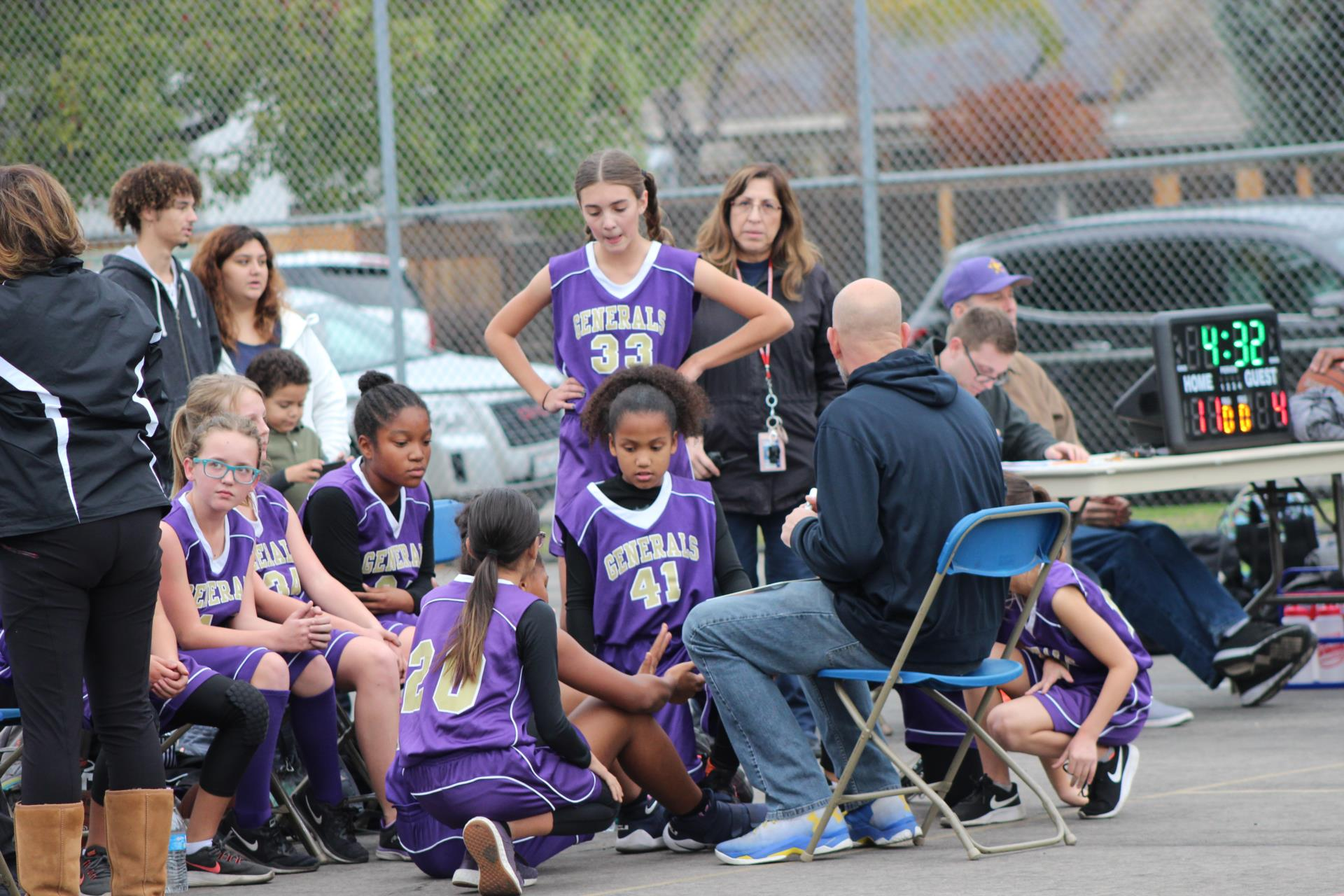 Girls gathered around coach listening.